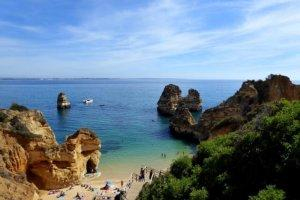 rock formations line the sandy beach of the Algarve Coast
