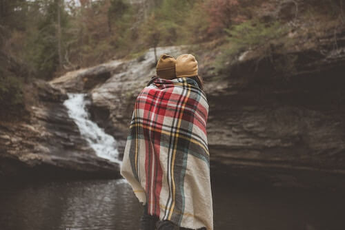 Couple with blanket in woods