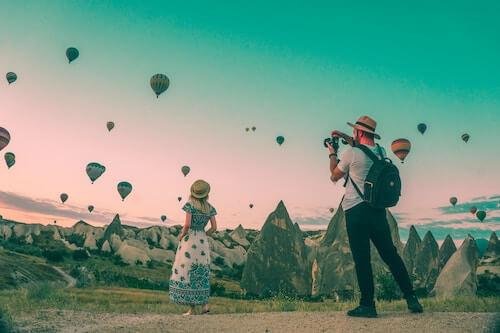 Man taking photo of woman and hot air balloons
