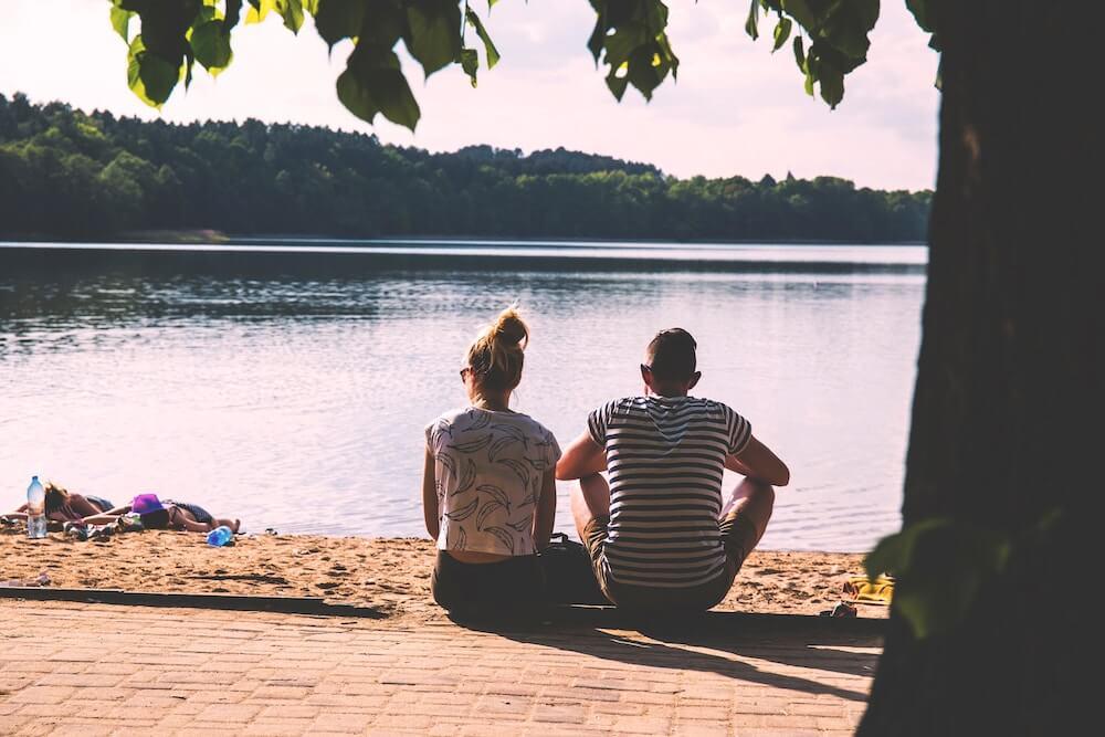 man and woman sitting at edge of lake