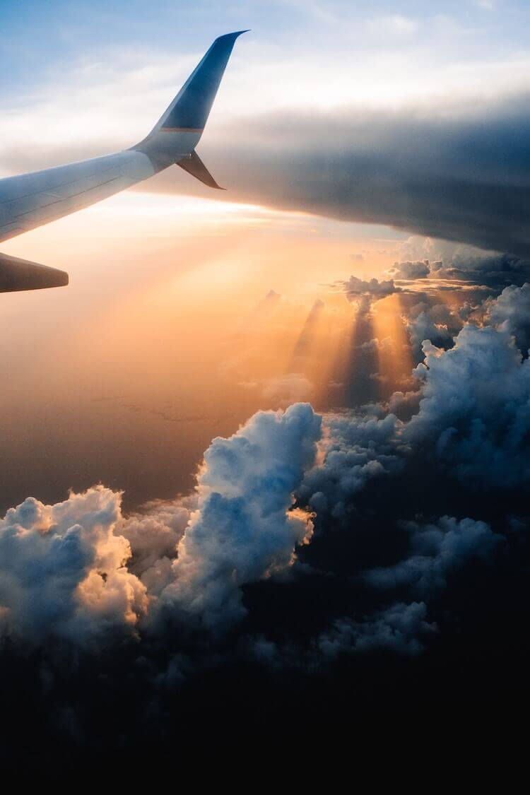 plane flying over clouds at sunset