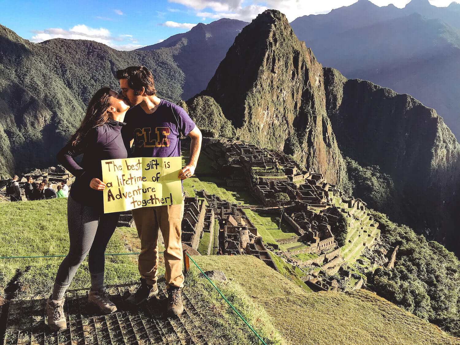 Kat and Chris holding a sign saying -The best gift is a lifetime of adventure together,- while kissing- overlooking Machu Picchu - Peru itinerary