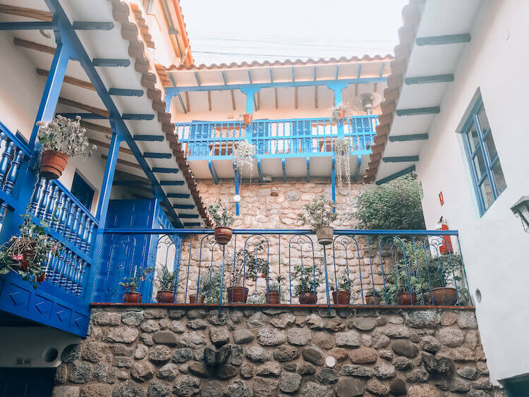 Rumi Wasi courtyard with blue railings and stone walls - Peru itinerary