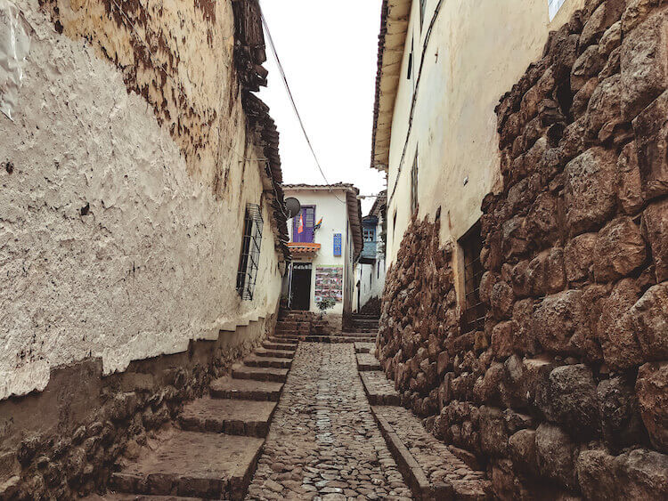 Streets of Cusco with incan stones with housing on top - Peru itinerary