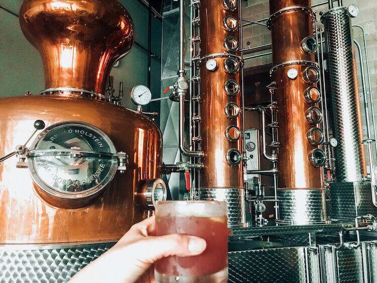 Drink in hand in front of the gin distiller at Hardshore Distilling