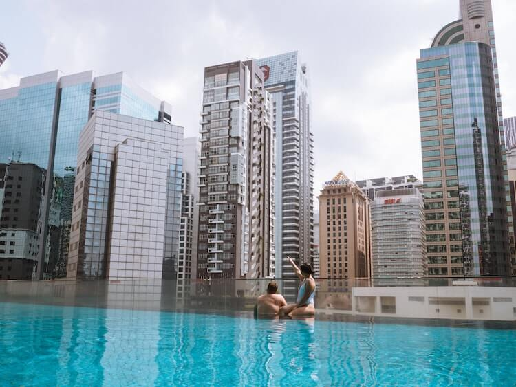 Couple enjoying the city view from a rooftop pool