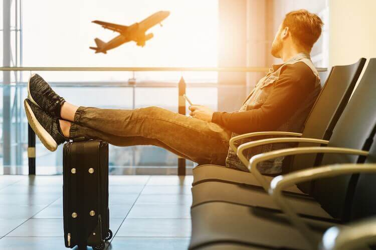 Man watching plane while sitting in airport with legs propped up on suitcase