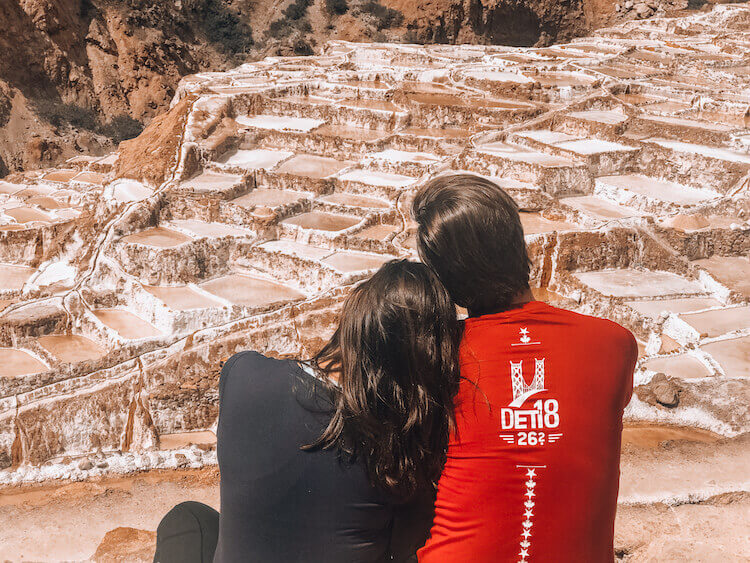 Kat and Chris sitting and relaxing while looking at the Maras Salt mines in Peru - Peru itinerary