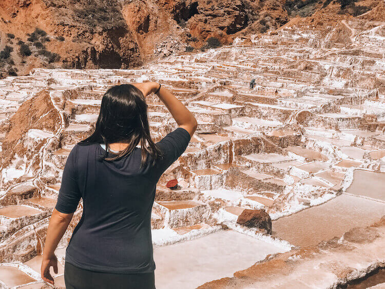 Woman staring off into the distance at the Maras Salt Mines in Peru - Peru itinerary