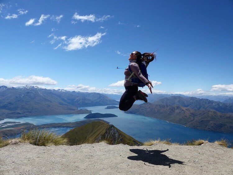 Christine jumping at Milford Sound, New Zealand