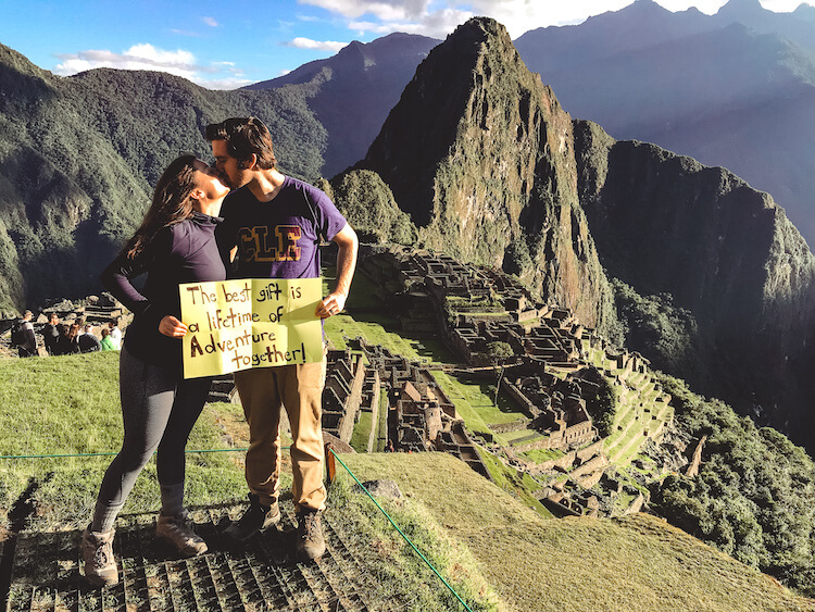 Kat and Chris holding sign at Machu Picchu