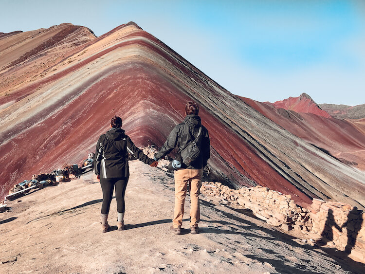 Kat and Chris standing in front of Rainbow Mountain facing it