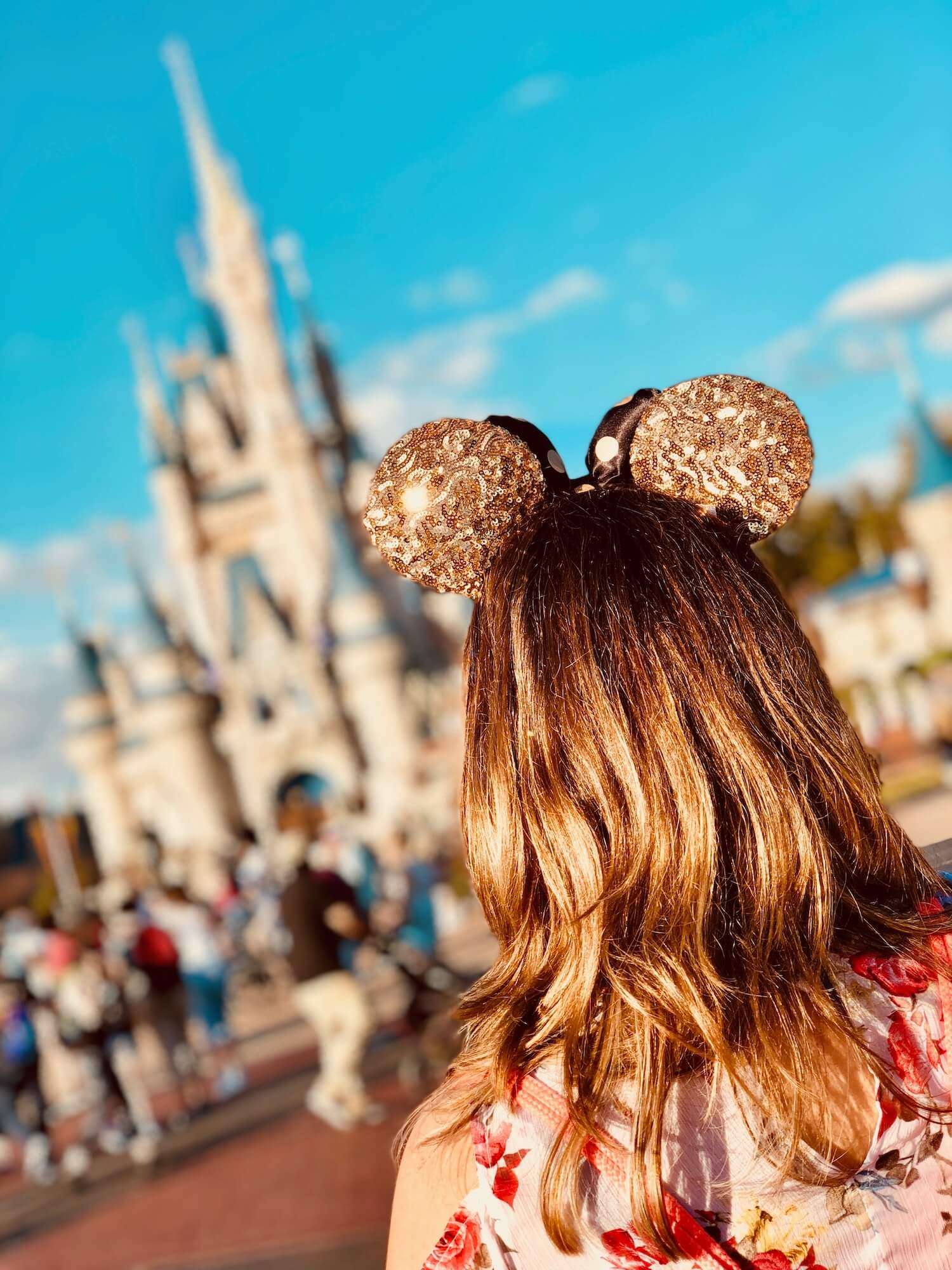 Girl with gold Disney ears in front of Cinderella's Castle at Disney World