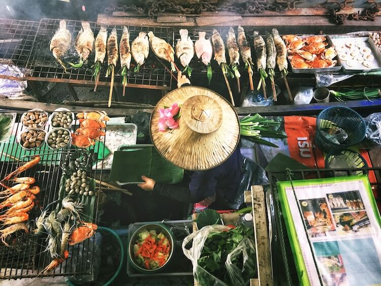 Woman grilling fish on a boat in Bangkok
