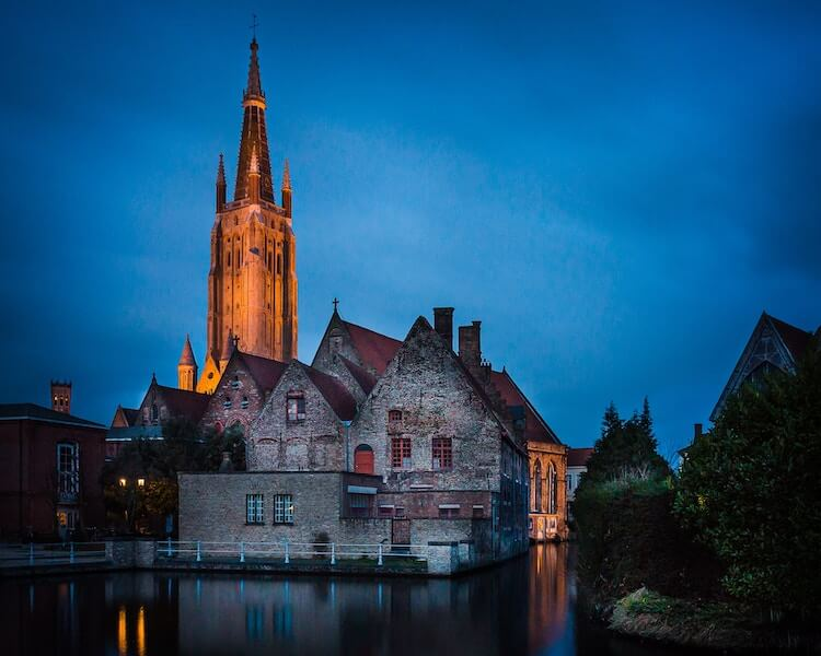 Bruges Belgium in the evening with the cathedral in the background and canals in forefront