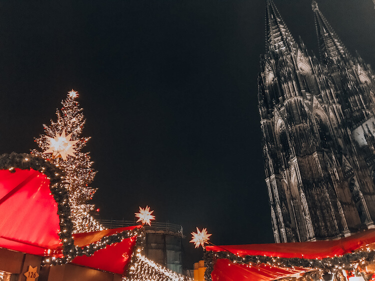 Cologne Cathedral Christmas Market at night with church and tree