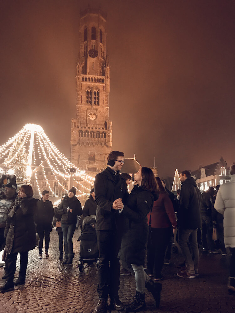 Kat and Chris at the Bruges Christmas market in front of the Belfry-Things to do in Bruges