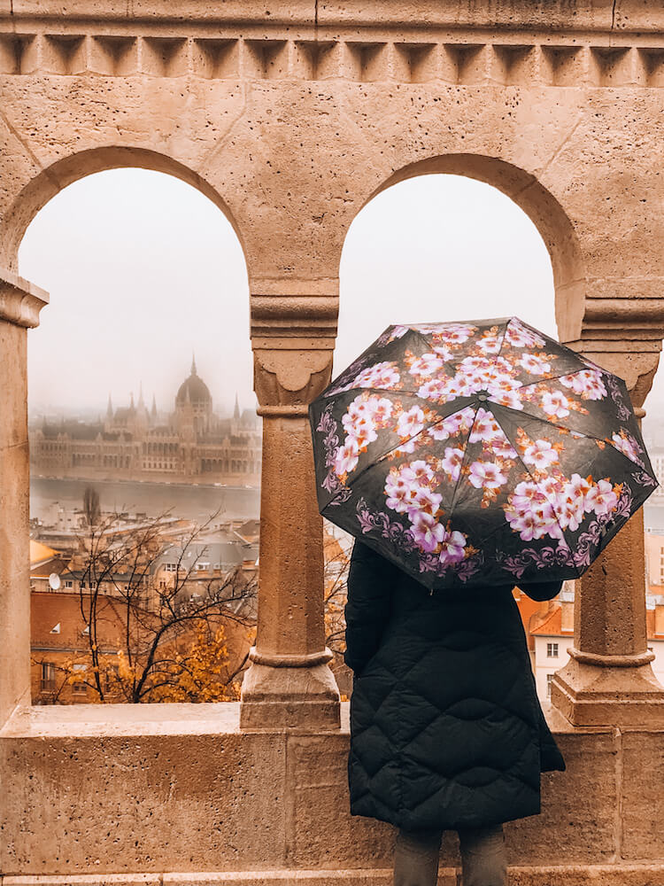 Kat looking out from Fisherman's Bastion in the rain toward the Hungarian Parliament Building
