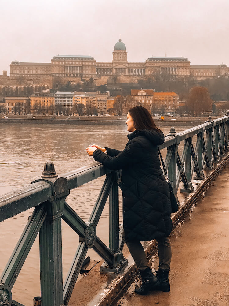 Kat staring at the Danube River from the Chain Bridge in Budapest - Top Things to do in Budapest