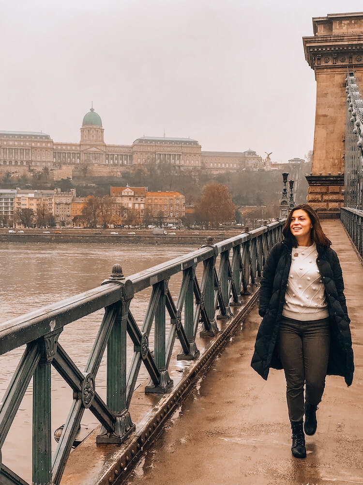 Kat walking in toward the camera on the Chain Bridge in Budapest