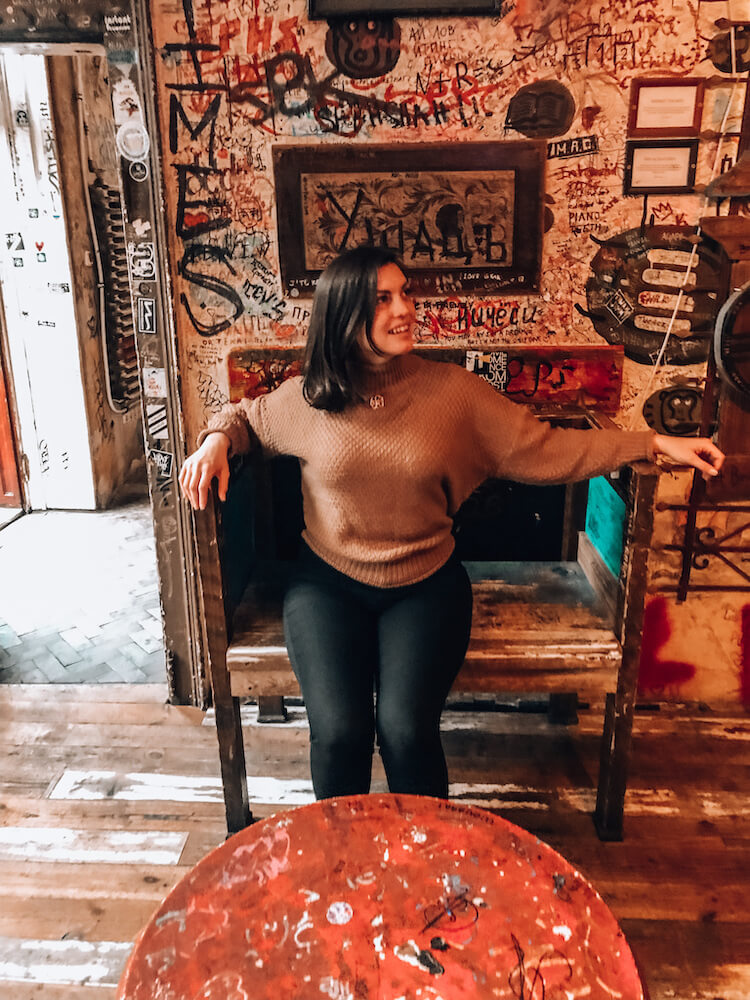 Kat wearing black trousers and a brown sweater sitting in a chair next to a graffiti wall at Szimpla Kert in Budapest, Hungary