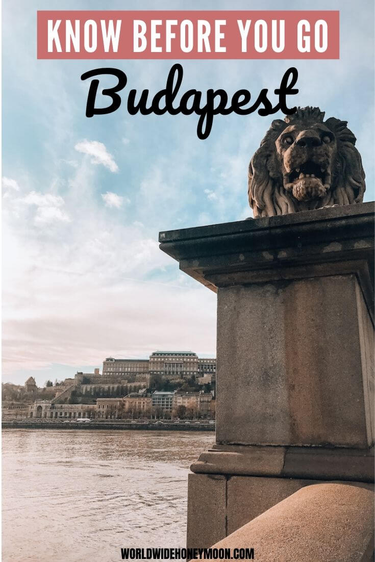 Know Before You Go Budapest | Photo pictured is the lion statue from the Chain Bridge in the foreground with the Danube River and Buda Castle in the background