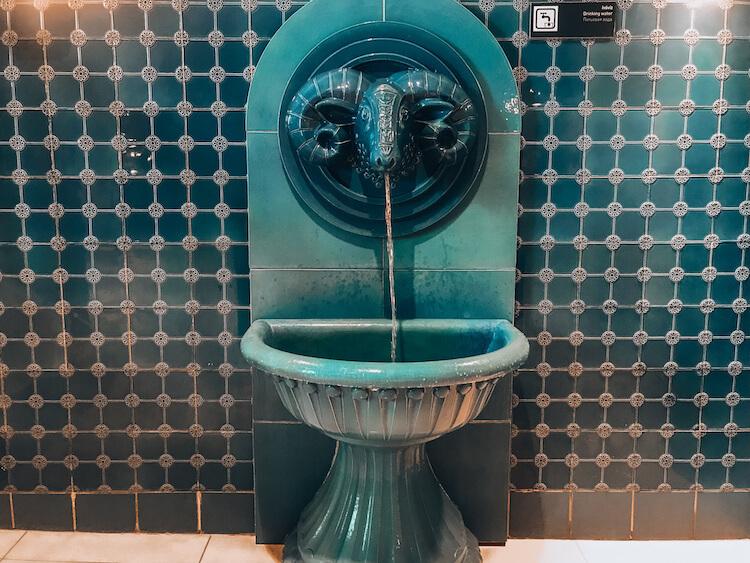 Water fountain made from a ceramic ram's head at Rudas Baths