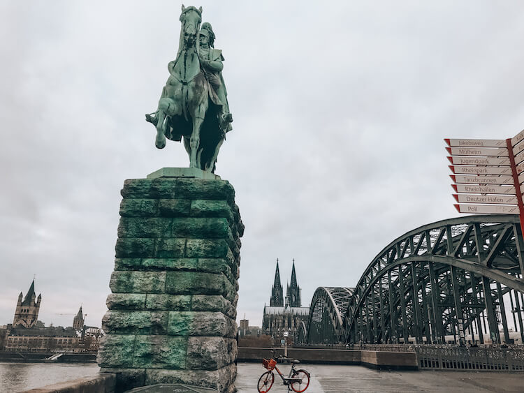 statue in front of the bridge and Cologne Cathedral