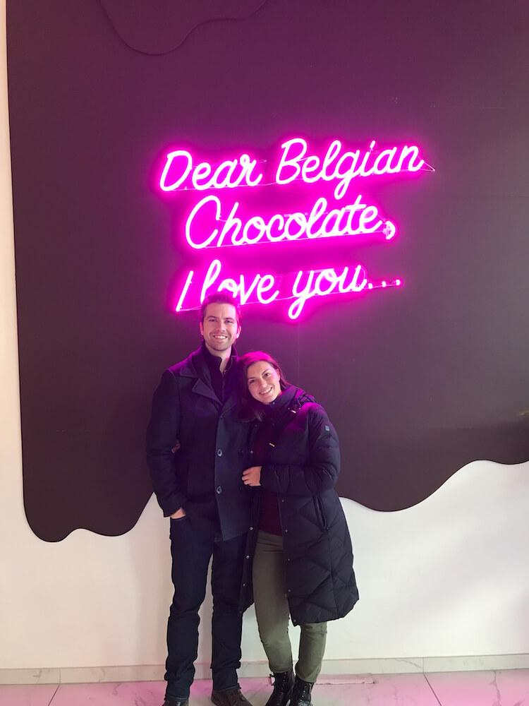 Kat and Chris in front of a sign saying -Dear Belgian Chocolate, I love you...- in Antwerp at Chocolate Nation