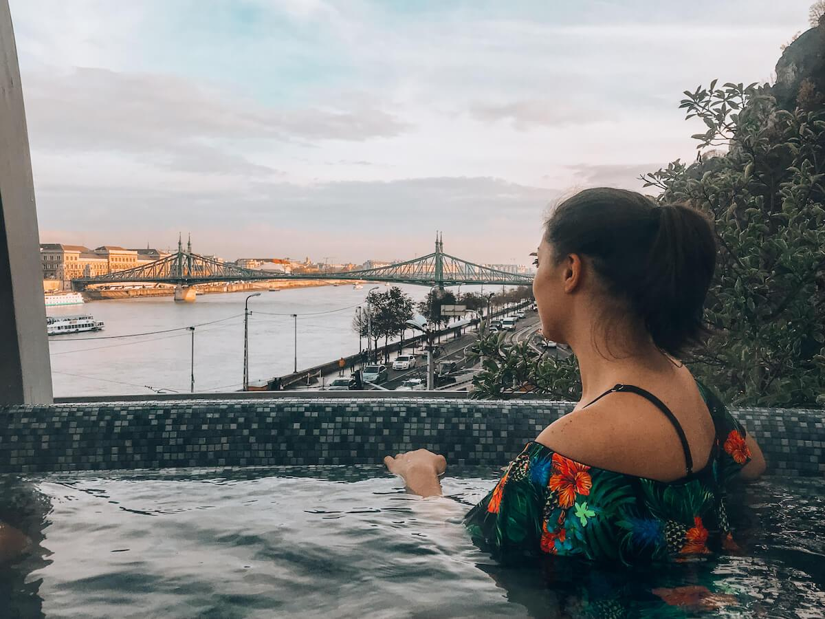 Kat looking out over the Danube River while sitting in the rooftop hot tub at Rudas Baths
