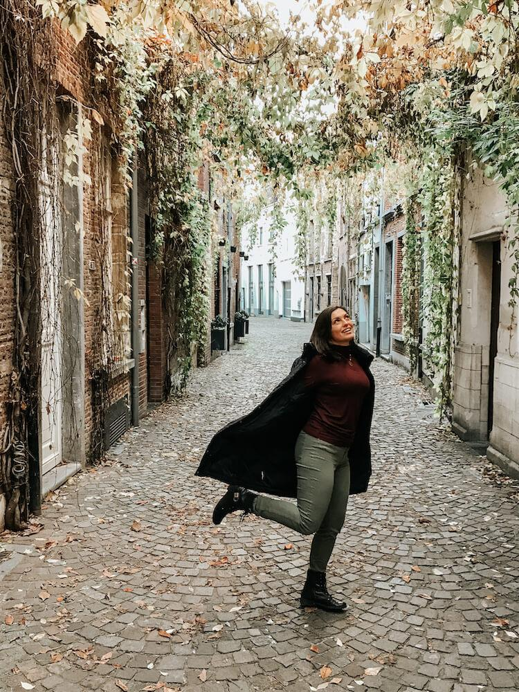 Kat twirling around under a canopy of plants on a cobblestone street in Antwerp- Antwerp in one day