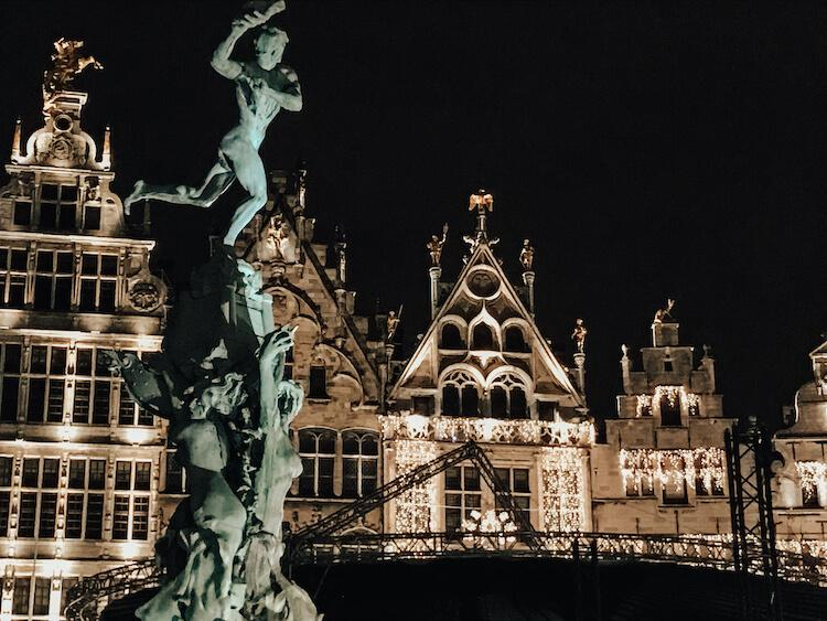 One Day in Antwerp at night with a statue of Brabo throwing the hand