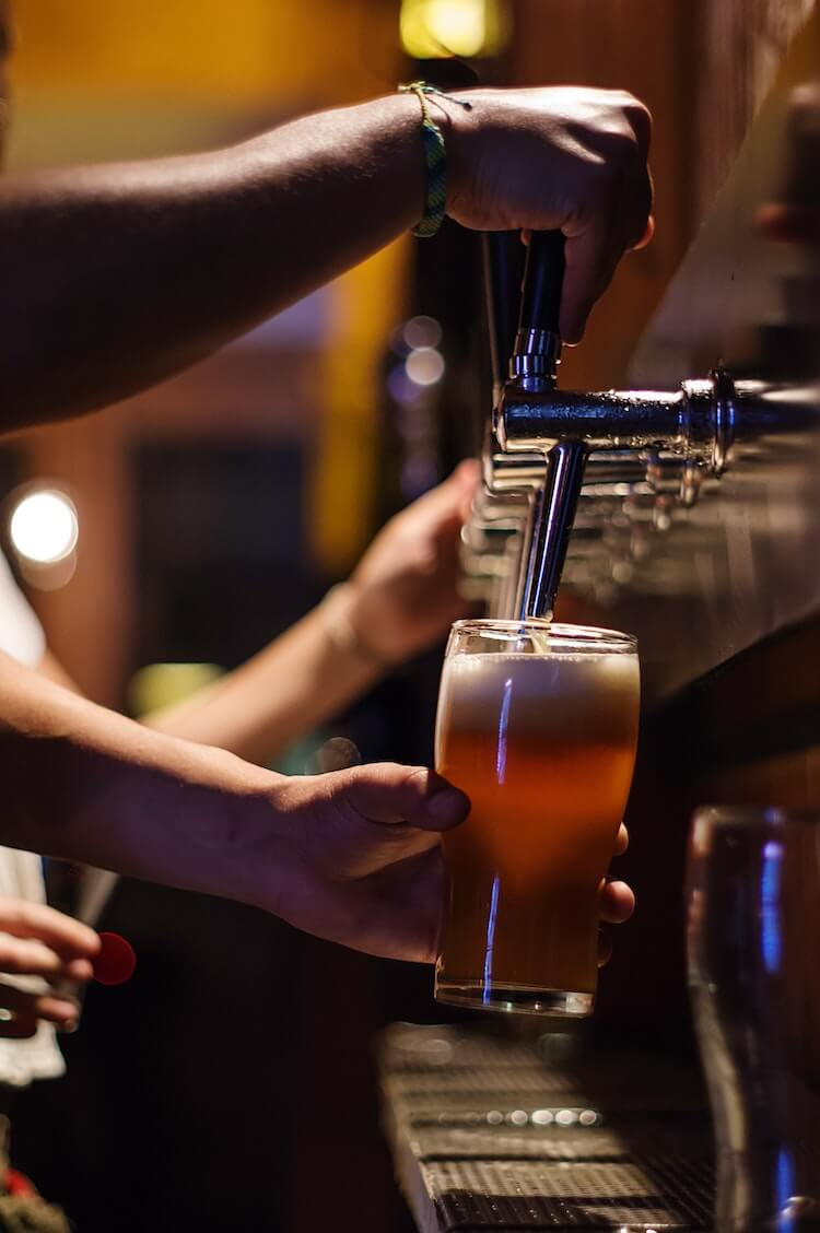 Bartender pouring a beer from a tap