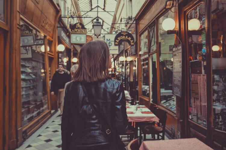 Girl wearing a black leather jacket in a covered market in Paris- What to Wear in Paris