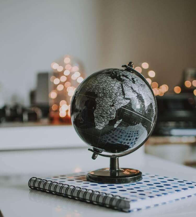 Globe on top of book with lights in the background- ways to bring travel to you at home