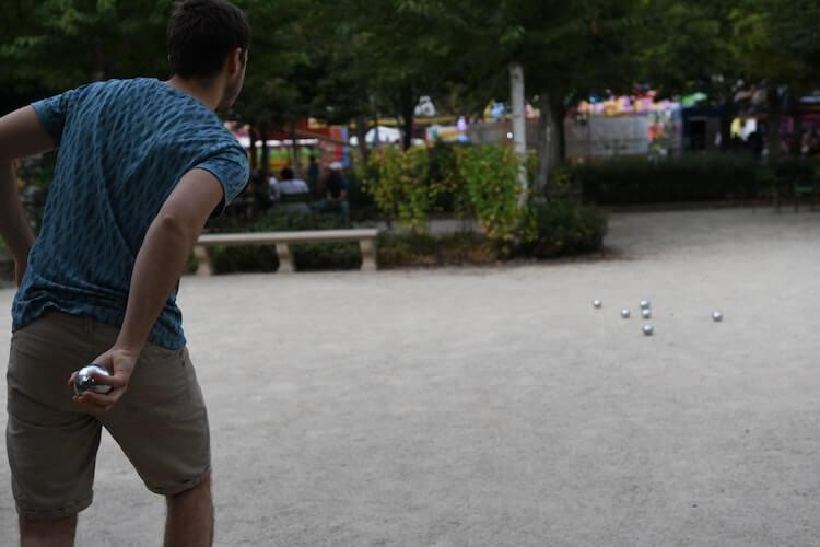 Man wearing a blue t-shirt and shorts playing in a park in Paris