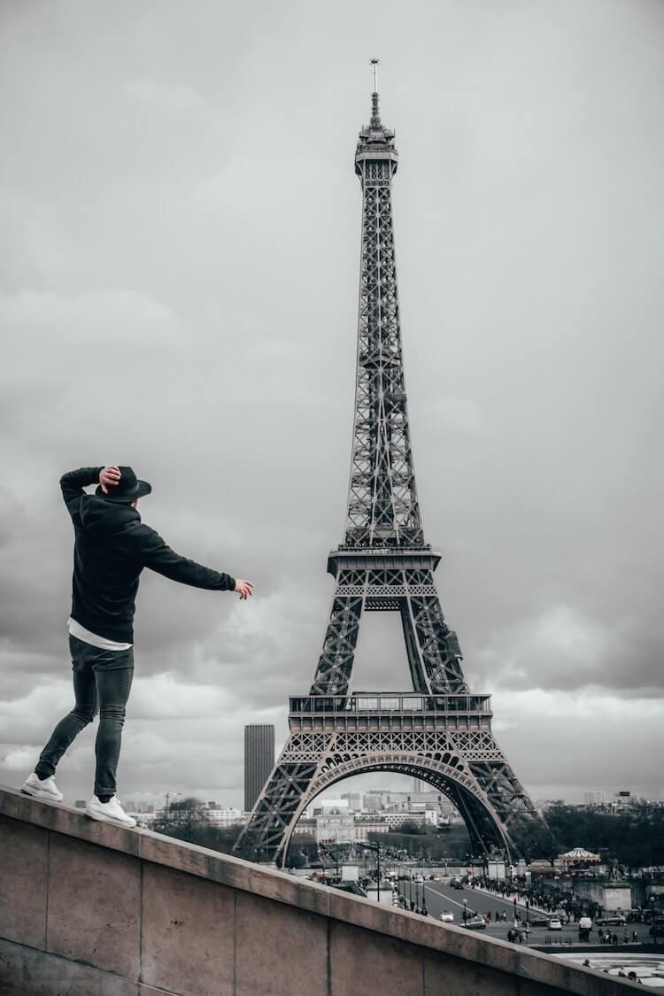 Man wearing jeans, sweater, and hat in front of the Eiffel Tower