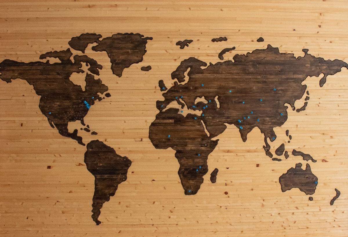 Pins on a wooden world map- how to travel while at home