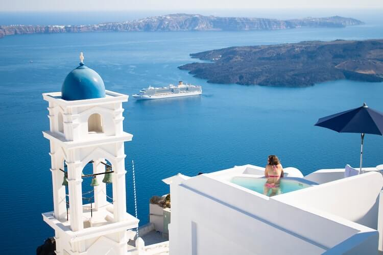 Woman in a plunge pool in Santorini- Couple's Travel Bucket List