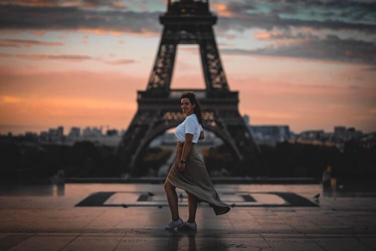Woman wearing a long skirt, white shoes, and white shirt in front of the Eiffel Tower