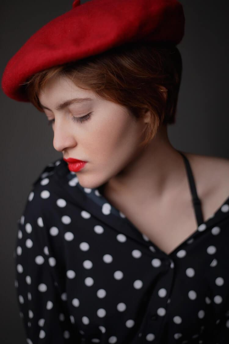Woman wearing red beret with red lipstick