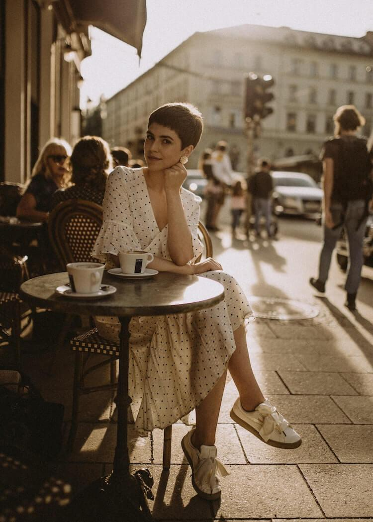 Woman wearing white shoes and a polka dot dress sitting at a sidewalk cafe