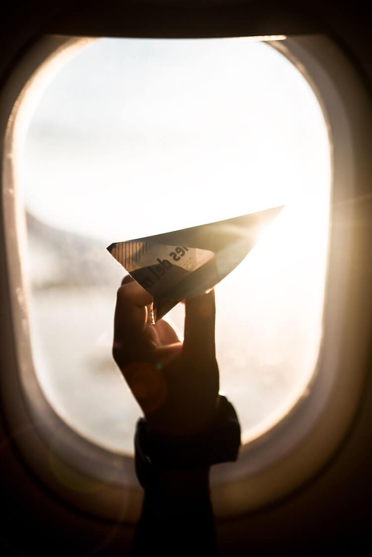 paper airplane next to a airplane window