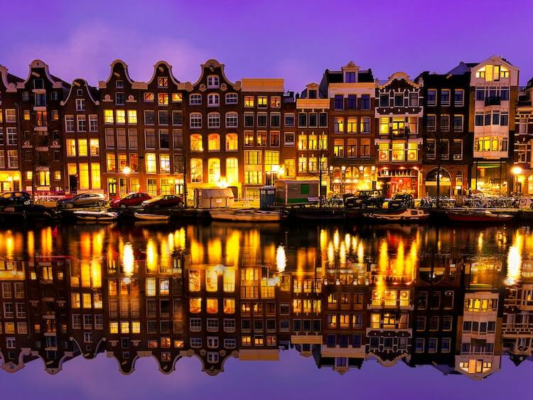 Amsterdam at twilight with the houses lit and reflecting on the canal