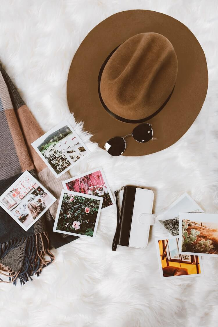 What Travel Bloggers are Thankful For - Brown Hat and Sunglasses with Travel Photos on a White Blanket