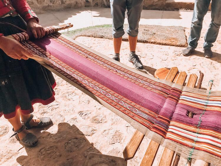 Peruvian local making a handmade Peruvian souvenir of an alpaca table runner