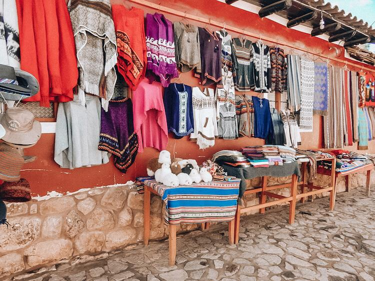Peruvian souvenirs at a market in the Sacred Valley including textiles, alpaca dolls, and scarves