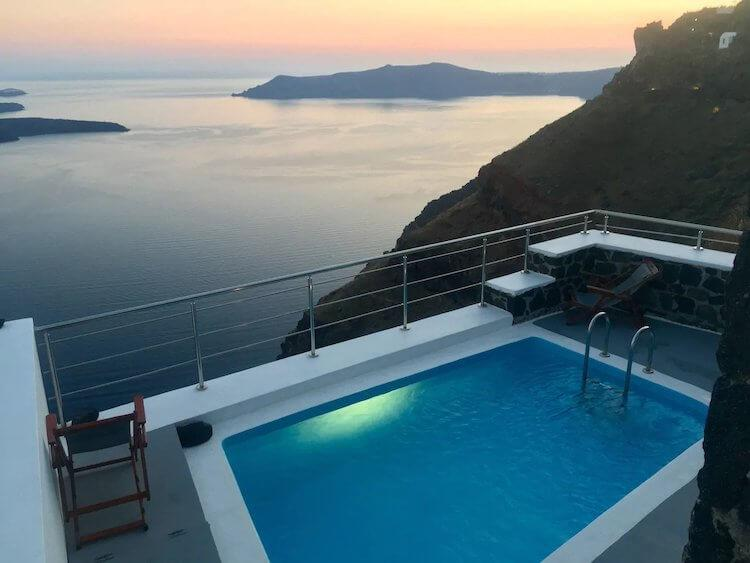 Aegean Sea at sunset in the background with a pool and balcony in the foreground