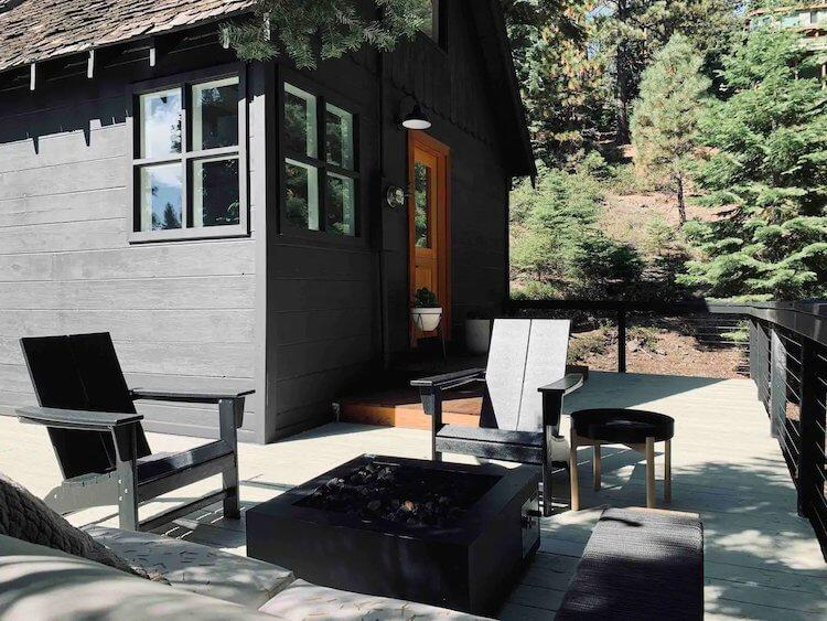 Black Cabin with black deck chairs around a modern firepit in Lake Tahoe