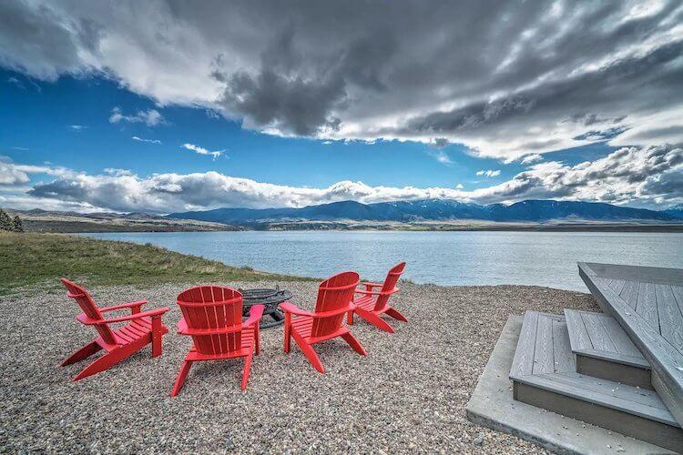 Red deck chairs arranged around a fire pit facing the lake and mountains in Montana